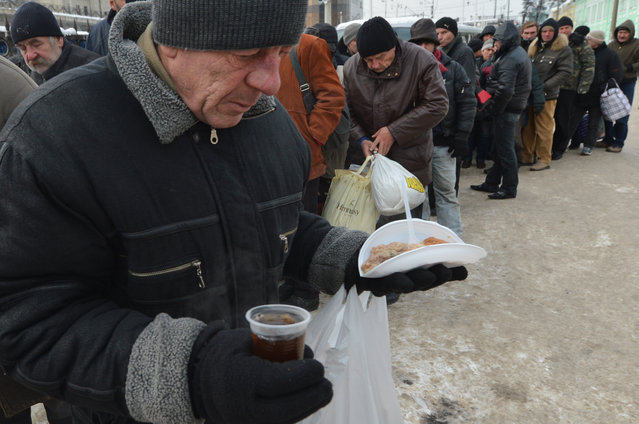 Homeless people queue to get free hot food organized by social services duringa frosty winter's day in Kiev on December 18, 2012. Nineteen people died of exposure in Ukraine in the last 24 hours amid temperatures of minus 20 degrees Celsius (minus 4 degrees Fahrenheit), bringing the toll this month to 37, the health ministry said Tuesday. (Photo by Sergei Supinsky/AFP Photo)