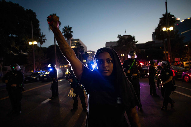 A woman holds up her fist in front of a row of Police officers during a protest demanding justice for George Floyd, Breonna Taylor and also in solidarity with Portland's protests, in Downtown Los Angeles, California, on July 25, 2020. (Photo by Apu Gomes/AFP Photo)