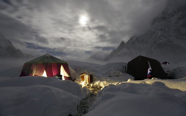 The moon illuminates the snow-covered Concordia, the confluence of the Baltoro and Godwin-Austen glaciers, near the world's second highest mountain the K2 (8,000 meters) in the Karakoram mountain range in Pakistan September 6, 2014. (Photo by Wolfgang Rattay/Reuters)