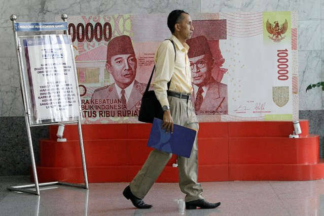 A man walks past a poster of an one hundred thousand rupiah bank note inside Indonesia's central bank, Bank Indonesia, in Jakarta, Indonesia July 21, 2016. REUTERS/Iqro Rinaldi