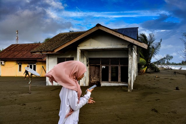 A girl walks past outside a house damaged by tidal waves at Meulaboh beach in Aceh province on July 12, 2020. (Photo by Chaideer Mahyuddin/AFP Photo)