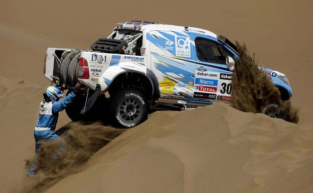 Argentine co-driver Bernardo Graue, left, and driver Lucio Alvarez, inside the vehicle, try to free their pick-up stuck on a dune during the 6th stage of the 2013 Dakar Rally. (Photo by Victor R. Caivano/Associated Press)