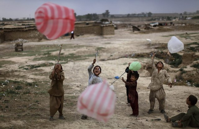 Pakistani children play with plastic bags in a slum area on the outskirts of Islamabad, Pakistan, Sunday, May 20, 2012. (Photo by Muhammed Muheisen/AP Photo)
