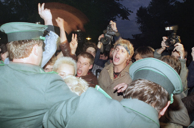 East German policemen, foreground, try to stop demonstrators from moving toward the East German parliament building, October 7, 1989 where Soviet President Mikhail S. Gorbachev attended a reception. Several thousand young people demanded democratic reforms in East Germany. (Photo by Jockel Finck/AP Photo)