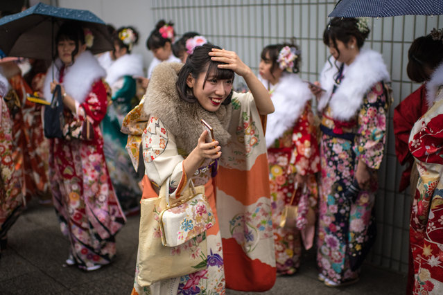 A woman tries to protect her hair from the rain as she joins friends after attending a Coming of Age ceremony on January 8, 2018 in Yokohama, Japan. (Photo by Carl Court/Getty Images)
