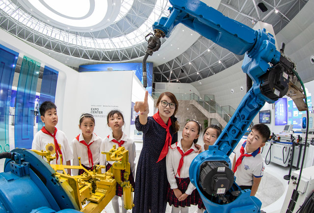 School children learn about the AI robotic arm. Haian City, Jiangsu Province, China, August 26, 2020. (Photo by Costfoto/Barcroft Media via Getty Images)