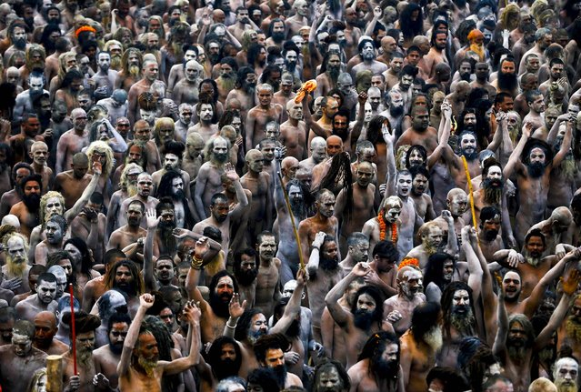 Naga Sadhus, or Hindu naked holy men, walk in procession after bathing at the confluence of the Hindu holy rivers the Ganges, during the Maha Kumbh festival in Allahabad, India, on February 15, 2013. (Photo by Kevin Frayer/Associated Press)