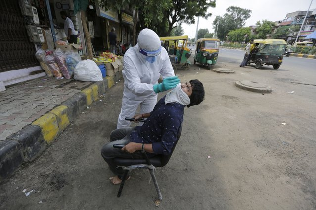 A health worker takes a nasal swab sample to test for COVID-19 in Ahmedabad, India, Tuesday, September 8, 2020. India's coronavirus cases are now the second-highest in the world and only behind the United States. (Photo by Ajit Solanki/AP Photo)