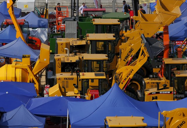Foreign visitors check construction vehicles on display during the China Import and Export Fair, also known as Canton Fair, in the southern Chinese city of Guangzhou October 15, 2015. (Photo by Bobby Yip/Reuters)