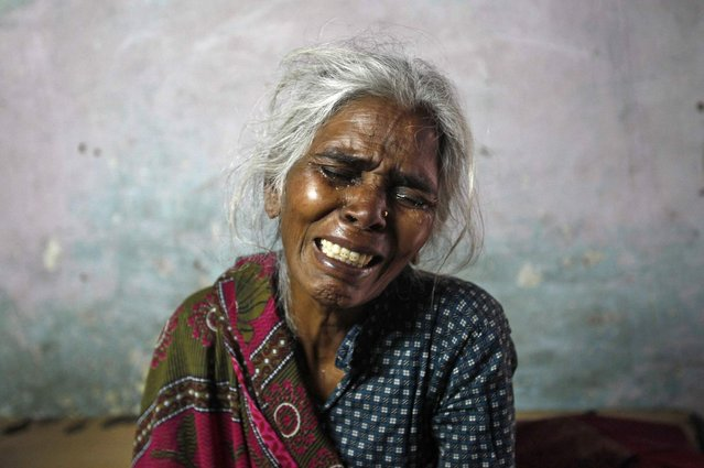 """Ram Bai, mother of Ram Singh, the driver of the bus in which a young woman was gang-raped and fatally injured three months ago, wails inside her house at Ravi Das camp in New Delhi March 11, 2013. Ram Singh hanged himself in his jail cell on Monday, prison authorities said, but his family and lawyer said they suspected """"foul play"""". Singh, the main accused in India's most high-profile criminal case, killed himself in a cell he shared with three other inmates in New Delhi's Tihar jail just before dawn, prison spokesman Sunil Gupta said. Ravi Das camp is the slum where four of the six accused in the rape case including Singh reside at. (Photo by Mansi Thapliyal/Reuters)"""