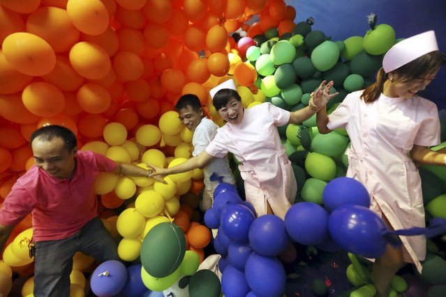 Participants walk among balloons during a stress-relief event organised by a shopping mall in Dongguan, Guangdong province, China, Ocotber 25, 2015. About 100 people joined the event on Sunday to try to burst 600,000 balloons in order to relieve stress, local media reported. (Photo by Reuters/China Daily)