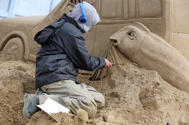 A sand sculptor works on a Jurassic Park themed sand sculpture as pieces are prepared as part of this year's Hollywood themed annual Weston-super-Mare Sand Sculpture festival on March 26, 2013 in Weston-Super-Mare, England. Due to open on Good Friday, currently twenty award winning sand sculptors from across the globe are working to create sand sculptures including Harry Potter, Marilyn Monroe and characters from the Star Wars films as part of the town's very own movie themed festival on the beach.  (Photo by Matt Cardy)