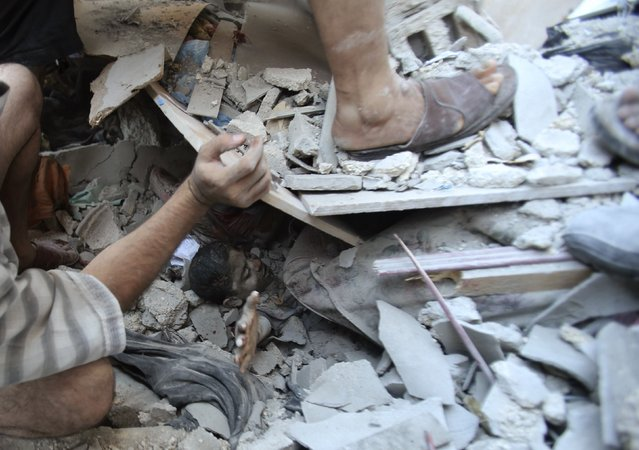 Palestinians rescue Mahmoud al-Ghol from under the rubble of a house in Rafah in the southern Gaza Strip, in this August 3, 2014 file photo. (Photo by Ibraheem Abu Mustafa/Reuters)
