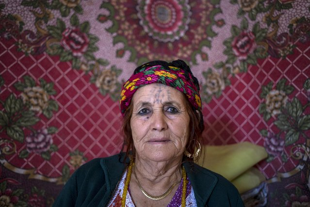 """Fatma Haddad, 80, a berber woman from the Chaouia region, who has facial tattoos, sits inside her house in Chalma in the Aures Mountain, Algeria October 9, 2015. Haddad was tattooed aged 18 by a local woman. """"I did it because all the girls my age were tattooed"""", Haddad said. Today she regrets being tattooed. Some believers have told these Muslim women that by allowing the tattoos they committed a sin according to Islam. (Photo by Zohra Bensemra/Reuters)"""