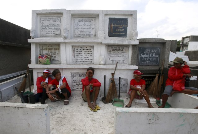 Street sweepers take a break in front of tombs inside a cemetery in Navotas city, north of Manila October 31, 2015. (Photo by Romeo Ranoco/Reuters)