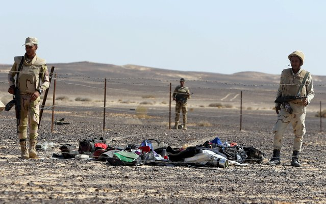 Egyptian army soldiers collect belongings of passengers from the crash site of a Russian airliner at the Hassana area in Arish city, north Egypt, November 1, 2015. (Photo by Mohamed Abd El Ghany/Reuters)
