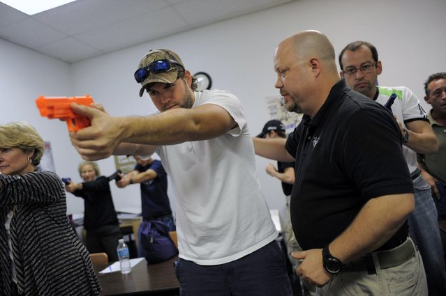Firearms instructor Mike Magowan (R) works with student Josh Meadows during a concealed weapons permit class at Take Aim Gun Range in Sarasota, Florida December 15, 2012.  The number of active concealed weapons licenses in Florida, already home to more owners of such registered weapons than any other U.S. state, is expected to reach the 1 million mark next week, a state official said on Wednesday. (Photo by Brian Blanco/Reuters)