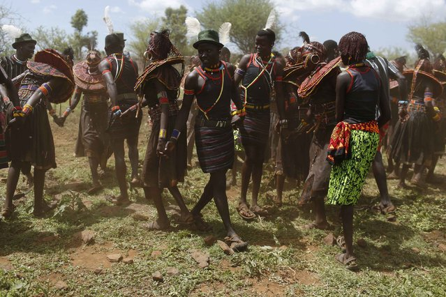 Pokot girls and boys dance together during an initiation ceremony of over a hundred girls passing over into womanhood, about 80 km (50 miles) from the town of Marigat in Baringo County December 6, 2014. (Photo by Siegfried Modola/Reuters)