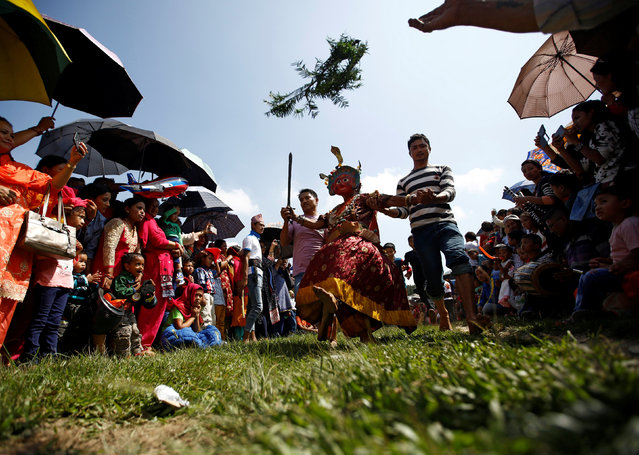 A medium dressed as a deity jumps during a trance while celebrating Shikali festival at Khokana village in Lalitpur, Nepal October 7, 2016. (Photo by Navesh Chitrakar/Reuters)