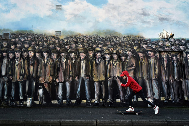 A skateboarder skates past a mural depicting Belfast shipyard workers near Sandy Row on March 1, 2018 in Belfast, Northern Ireland. The Titanic workers mural by artist Ed Reynolds was commissioned by Belfast City Council. Reynolds has worked on various visual schemes with the council including the Re-Imagining Communities project. Belfast has a strong history of murals associated with division, political and religious affiliation however the last few years have seen a growing re-imagining of the city landscapes open spaces. (Photo by Charles McQuillan/Getty Images)