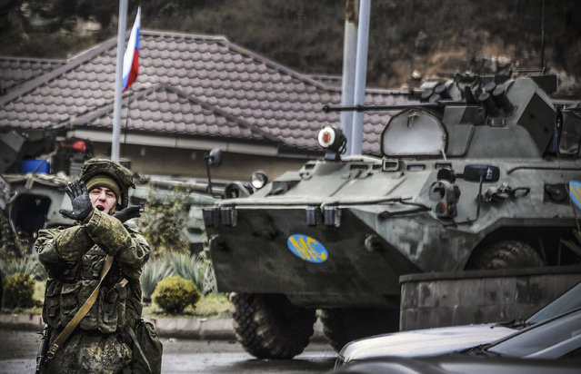 "A Russian peacekeeper shouts ""No pictures!"" at a checkpoint outside the city of Stepanakert on November 13, 2020, during a ceasefire in the military conflict between Armenia and Azerbaijan over the breakaway region of Nagorno-Karabakh. Russian began deploying 2,000 peacekeepers to Nagorno-Karabakh on November 10 after Armenia and Azerbaijan agreed a peace deal to end weeks of fierce fighting over the disputed region. The Moscow-brokered agreement came after a string of Azerbaijani victories in its fight to retake the ethnic Armenian enclave. It sparked celebrations in Azerbaijan but fury in Armenia, where protesters took to the streets to denounce their leaders for losses in the territory, which broke from Azerbaijan's control during a war in the early 1990s. (Photo by Alexander Nemenov/AFP Photo)"