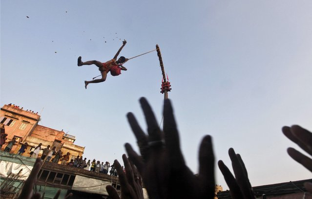 """A Hindu devotee hanging from a rope throws offering towards other devotees during the """"Chadak"""" ritual in Kolkata April 14, 2013. Hundreds of Hindu devotees attend the ritual, held to worship the Hindu deity of destruction Lord Shiva, on the last day of the Bengali calendar year. (Photo by Rupak De Chowdhuri/Reuters)"""
