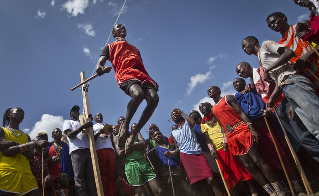 A Maasai warrior makes the high jump, in which athletes must touch a high line with the top of their heads, at the annual Maasai Olympics in the Sidai Oleng Wildlife Sanctuary near to Mt. Kilimanjaro, in southern Kenya, Saturday, December 13, 2014. (Photo by Ben Curtis/AP Photo)