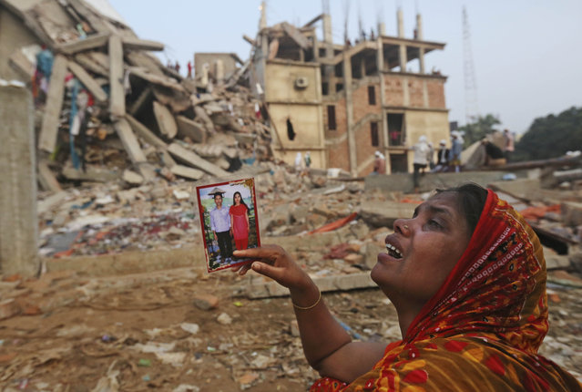A Bangladeshi woman weeps as she holds a picture of her and her missing husband as she waits at the site of a building that collapsed Wednesday in Savar, near Dhaka, Bangladesh, Friday, April 26, 2013. The death toll reached hundreds of people as rescuers continued to search for injured and missing, after a huge section of an eight-story building that housed several garment factories splintered into a pile of concrete. (Photo by Kevin Frayer/AP Photo)