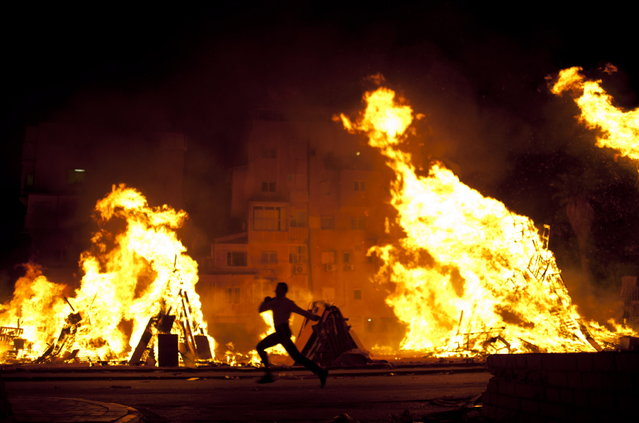 An Ultra-Orthodox Jewish boy runs past bonfires during Lag Ba'Omer celebrations to commemorate the end of a plague said to have decimated Jews in Roman times, in Bnei Brak near Tel Aviv, Israel, Saturday, April 27, 2013. (Photo by Ariel Schalit/AP Photo)