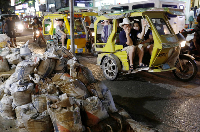 Tourists ride tricycles past the uncollected sacks containing waste from the sewers along a road at Boracay in Philippines on April 9, 2018. (Photo by Erik De Castro/Reuters)