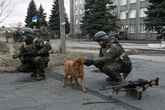 A Ukrainian serviceman plays with a dog as he and his comrade patrol the street in the eastern Ukrainian town of Debaltseve in Donetsk region, December 24, 2014. (Photo by Valentyn Ogirenko/Reuters)
