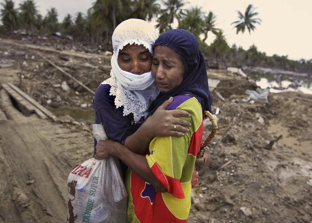 In this January 9, 2005 file photo, Norhayati, right, and her niece Ita cry as they embrace when meeting for the first time since the tidal wave left a trail of destruction in a small village on the outskirts of Banda Aceh, Sumatra island, Indonesia. (Photo by Peter Dejong/AP Photo)