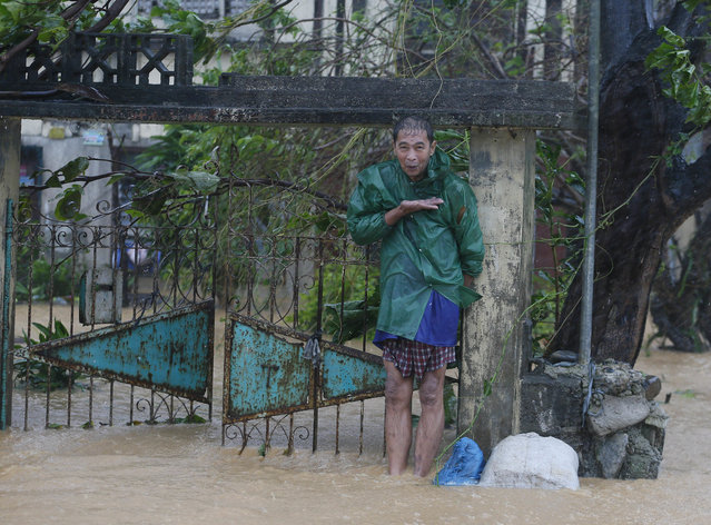 A man shows the height of his flooded home as Super Typhoon Haima lashes Narvacan township, Ilocos Sur province, Philippines, Thursday, October 20, 2016. Super Typhoon Haima slammed into the northeastern Philippine coast late Wednesday with ferocious winds and rain that rekindled fears and memories from the catastrophe wrought by Typhoon Haiyan in 2013. (Photo by Bullit Marquez/AP Photo)