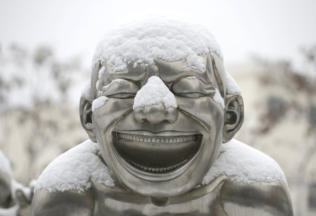 A part of a sculpture by Chinese artist Yue Minjun is covered by snow beside a road in Beijing, China, November 22, 2015. (Photo by Jason Lee/Reuters)