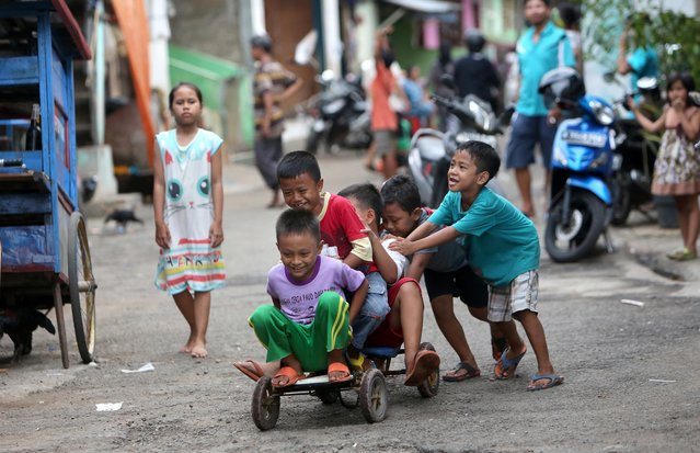 Children play a bicycle at a slum area in Jakarta, Indonesia, Tuesday, September 13, 2016, in Jakarta, Indonesia. (Photo by Tatan Syuflana/AP Photo)