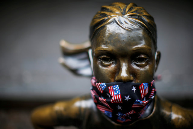"A protective mask is seen on the face of the ""Fearless Girl"" sculpture in the financial district, during the outbreak of the coronavirus disease (COVID-19) in New York City, New York, U.S. April 23, 2020. (Photo by Eduardo Munoz/Reuters)"
