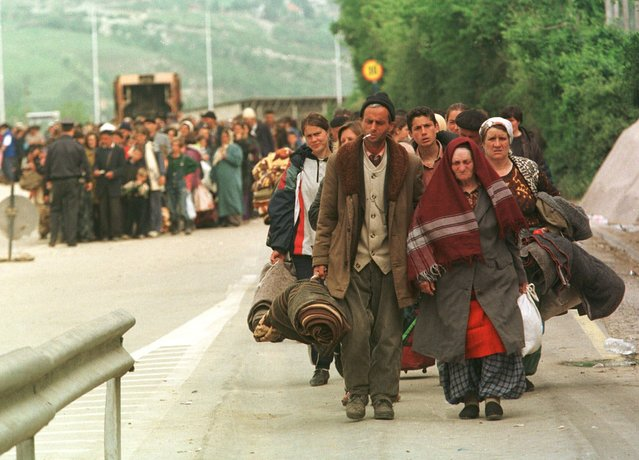 Ethnic Albanian refugees cross the Kosovo-Macedonia border at the Blace checkpoint, Tuesday, May 4, 1999. More than 675,000 ethnic Albanians have poured out of Kosovo since the NATO airstrikes began on March 24, many say they were forced out by roving bands of Serbs and are alleging mass atrocities. Thousands more refugees streamed out to Albania and Macedonia on Monday. (Photo by John McConnico/AP Photo)