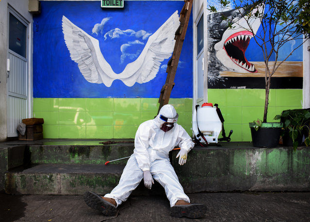 A health agency official, seen alongside his disinfectant dispenser, rests by the entrance to a public toilet as other colleagues (not pictured) conduct polymerase chain reaction (PCR) testing for the COVID-19 coronavirus at a bus station in Bandung, West Java, on May 13, 2020. (Photo by Timur Matahari/AFP Photo)