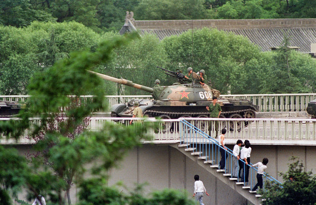 Chinese onlookers run away as a soldier threatens them with a gun on June 5, 1989 as tanks took position at Beijing's key intersections next to the diplomatic compound. (Photo by Catherine Henriette/AFP Photo)