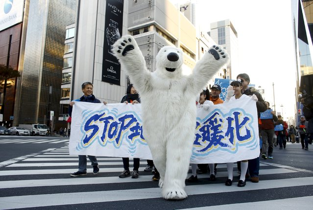 A man in polar bear costume leads a march of people through central Tokyo ahead of the 2015 Paris Climate Conference, known as the COP21 summit, November 28, 2015. Ahead of the U.N. climate change summit in Paris starting this week, about 1,000 citizens and environmental activists took to the streets of Tokyo on Saturday, calling for strong actions to combat global warming. (Photo by Thomas Peter/Reuters)