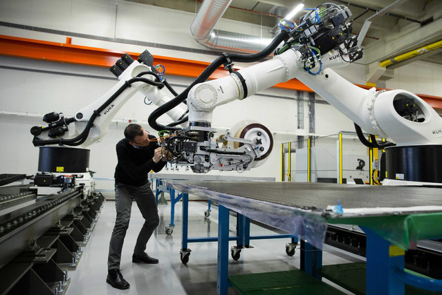 A man works on a robot at the first digital fabric of the Netherlands, an initiative of Siemens and Airborne in The Hague, The Netherlands, 01 December 2015. In the fabric carbons plates are produced for the aircraft industry. (Photo by Bart Maat/EPA)