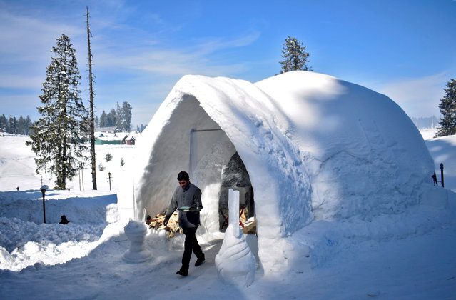"""A waiter comes out of """"Igloo Cafe"""", a cafe prepared with snow and ice, after serving customers at Gulmarg, a ski resort and one of the main tourist attractions in Kashmir region, January 28, 2021. (Photo by Sanna Irshad Mattoo/Reuters)"""