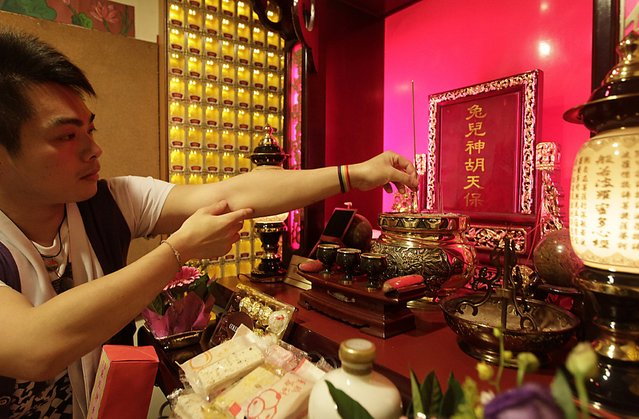 A worshipper offers incense sticks at the Wei-ming temple in New Taipei city January 8, 2015. The shrine, down a narrow alleyway in a bustling district of the city, is dedicated to a deity who has watched over homosexuals for four centuries. (Photo by Pichi Chuang/Reuters)