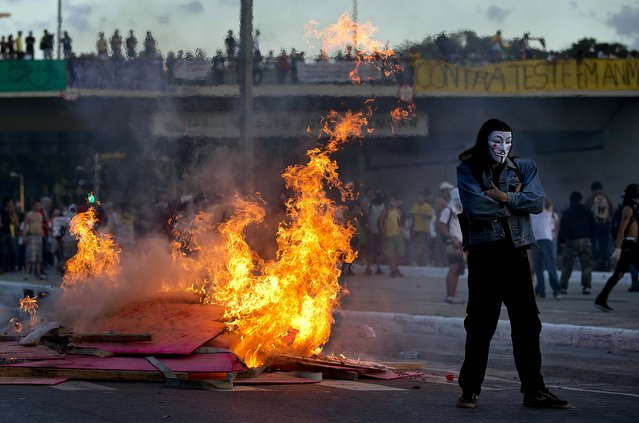 A protester stands by a burning barricade  during a demonstration in Belo Horizonte, Brazil, on June 26, 2013.  Anti-government protesters, in part angered by the billions spent in World Cup preparations, and police clashed Wednesday near the stadium hosting a Confederations Cup soccer match, with tens of thousands of demonstrators trying to march on the site confronting police firing tear gas and rubber bullets. (Photo by Victor R. Caivano/Associated Press)