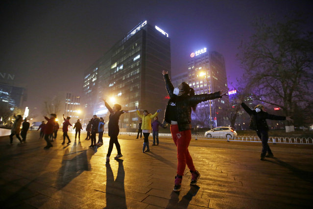 "Women wearing masks and other residents dance during their daily exercise amid the heavy smog in Beijing, China December 7, 2015. China's capital on Monday issued its first ever ""red alert"" for pollution, as the city government warned that Beijing would be shrouded in heavy smog from Tuesday until Thursday. (Photo by Jason Lee/Reuters)"