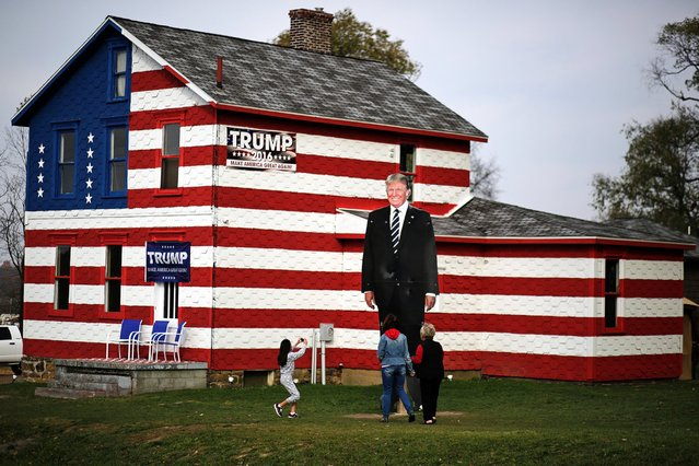 A young visitor takes a photo of a giant cutout of Republican candidate for president Donald Trump in front of the Trump House owned by Lisa Rossi in Youngstown, Pa., Tuesday, November 8, 2016. (Photo by Gene J. Puskar/AP Photo)