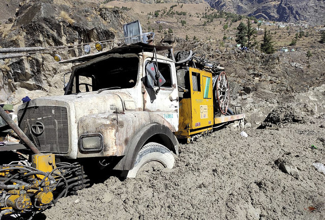 A hydro project vehicle is seen stuck in slash and mud at Reni village in the Tapovan area of Chamoli district, in Indian state of Uttrakhund, Monday, February 8, 2021. Rescuers were working Monday to rescue more than three dozen power plant workers trapped in a tunnel after part of a Himalayan glacier broke off Sunday and sent a wall of water and debris rushing down the mountain. (Photo by AP Photo/Stringer)