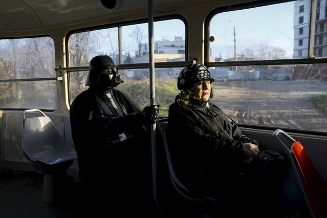 Darth Mykolaiovych Vader, who is dressed as the Star Wars character Darth Vader, poses for a picture as he rides on a tram in Odessa, Ukraine, December 3, 2015. (Photo by Valentyn Ogirenko/Reuters)
