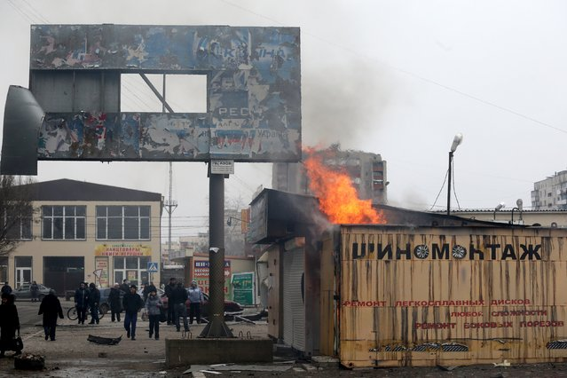 Peole look at a burning shop after shelling   in the southern Ukrainian port city of Mariupol on 24, 2015. (Photo by AFP Photo/Stringer)