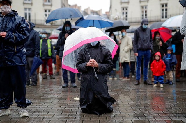 Parishioners wearing protective face masks pray at Graslin square during an open air mass in Nantes, as public masses are suspended during the second national lockdown as part of the measures to fight a second wave of the coronavirus disease (COVID-19), in France, November 15, 2020. (Photo by Stephane Mahe/Reuters)